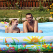 Young pair bathes in inflatable pool - Stock Photo
