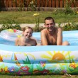 Young pair bathes in inflatable pool — Stock Photo