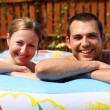 Young pair bathes in inflatable pool - Photo