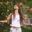 Happy girl throwing autumn leaves — Stock Photo