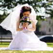 Young beautiful bride in summer park - Stock Photo