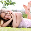 Woman lying on grass field at the park — Stock Photo #3625973