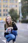 Girl starts up soap bubbles — Stock Photo
