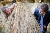 Wedding couple behind hay stack — Stock Photo