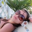 Girl in sun glasses has a rest near pool - Stock Photo