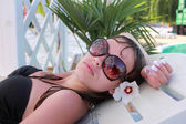 Girl in sun glasses has a rest near pool — Stock Photo