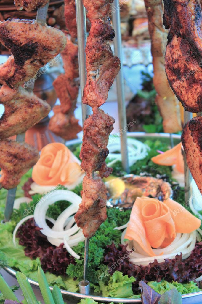 Georgian shish kebab on skewers are decorated by greens — Stock Photo #3855357