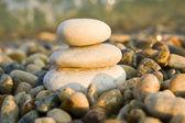 Three balanced rocks contrast a sea of stones — Stock Photo