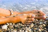 Woman's foot with the sea shell bracelet — Zdjęcie stockowe