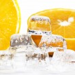 Six ice cubes melted in water and slices of orange — Stock Photo