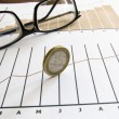 Stock chart with coinand glasses - Stock Photo