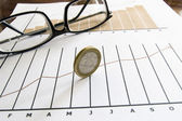 Stock chart with coinand glasses — Stock Photo