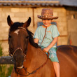 Child on brown horse - Foto Stock