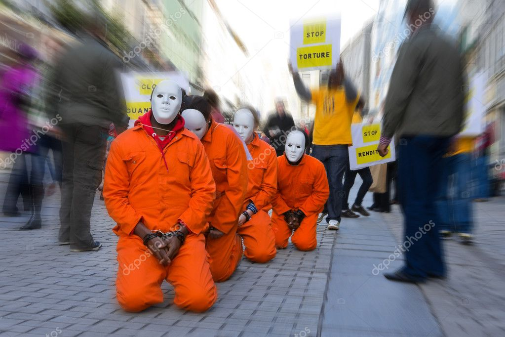 Group of in orange prison dress and white masks with bind hands kneeled at the crowded street — Stock Photo #3125014