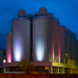 Row industrial metal distillery tanks at night - Stok fotoğraf