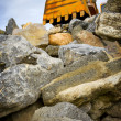Excavator detail on top of stones - Stock Photo