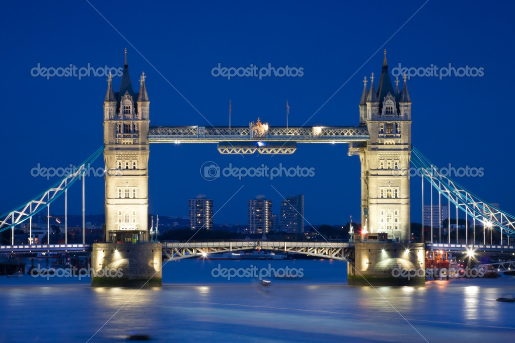 London's Tower Bridge illuminated at night time and reflections in water  Stock Photo #3634086
