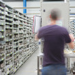 Shelves with spar parts and technician in motion — Stock Photo