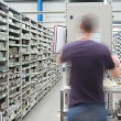 Shelves with spar parts and technician in motion — Stock Photo #3724082
