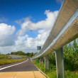 Road with protective metal side fence and sky - Stock Photo