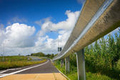 Road with protective metal side fence and sky — Stock Photo