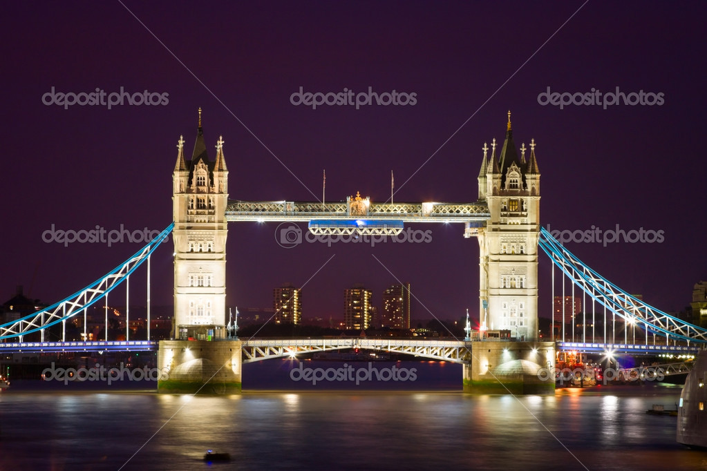 London's Tower Bridge illuminated at night time and reflections in water  Stock Photo #3724181