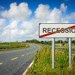 Road with recession sign crossed with red line - Stock Photo