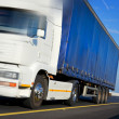 Truck with blue tent in motion — Stockfoto