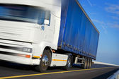 Truck with blue tent in motion — Stock Photo