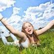 Pretty smiling girl relaxing outdoor in green grass — Stock Photo