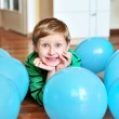 Boy laying with balloons — Stock Photo
