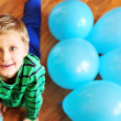 Boy laying on wooden floor with balloons — Stock Photo