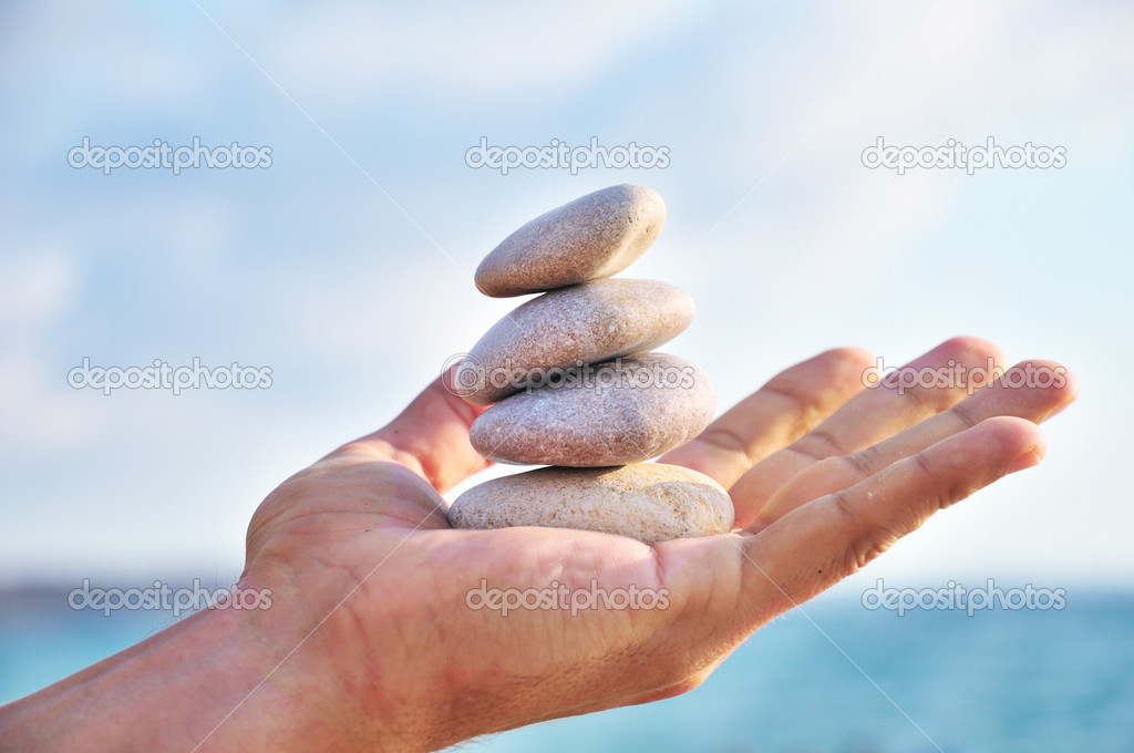 Balancing stones in man's palm over blue sky — Stock Photo #2889282