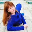 Redheaded girl laying on the pier - Stock Photo