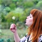 Beautiful girl blowing on dandelion — Stock Photo #2943694