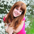 Redheaded girl in blossom garden — Stock Photo