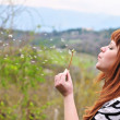 Girl blowing on dandelion outdoors — Stock Photo #3817259