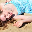 Laughing girl laying on the send — Stock Photo #3817284