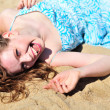 Stock Photo: Laughing girl laying on the send