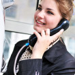 Happy teen talking by public  telephone - Stock Photo