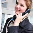 Happy teen talking by public telephone — Stock Photo #3817639