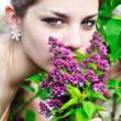 Beautiful teen girl smelling lilac blossoms — Stock Photo #3817738