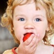 Little girl eating strawberry — Stock Photo