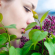 Teen girl smelling lilac blossoms - Stock Photo