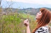 Flicka som blåser på maskros utomhus — Stockfoto