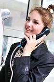 Happy teen talking by public telephone — Stock Photo