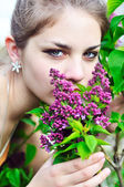 Beautiful teen girl smelling lilac blossoms — Stock Photo