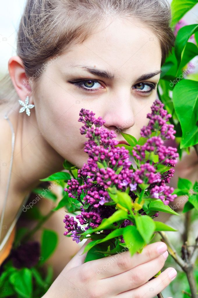 Beautiful teen girl smelling lilac blossoms - close up — Stok fotoğraf #3817738
