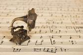 Gramophone on old sheet music — Stock Photo