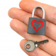 Lock with heart and key in hand — Stok fotoğraf